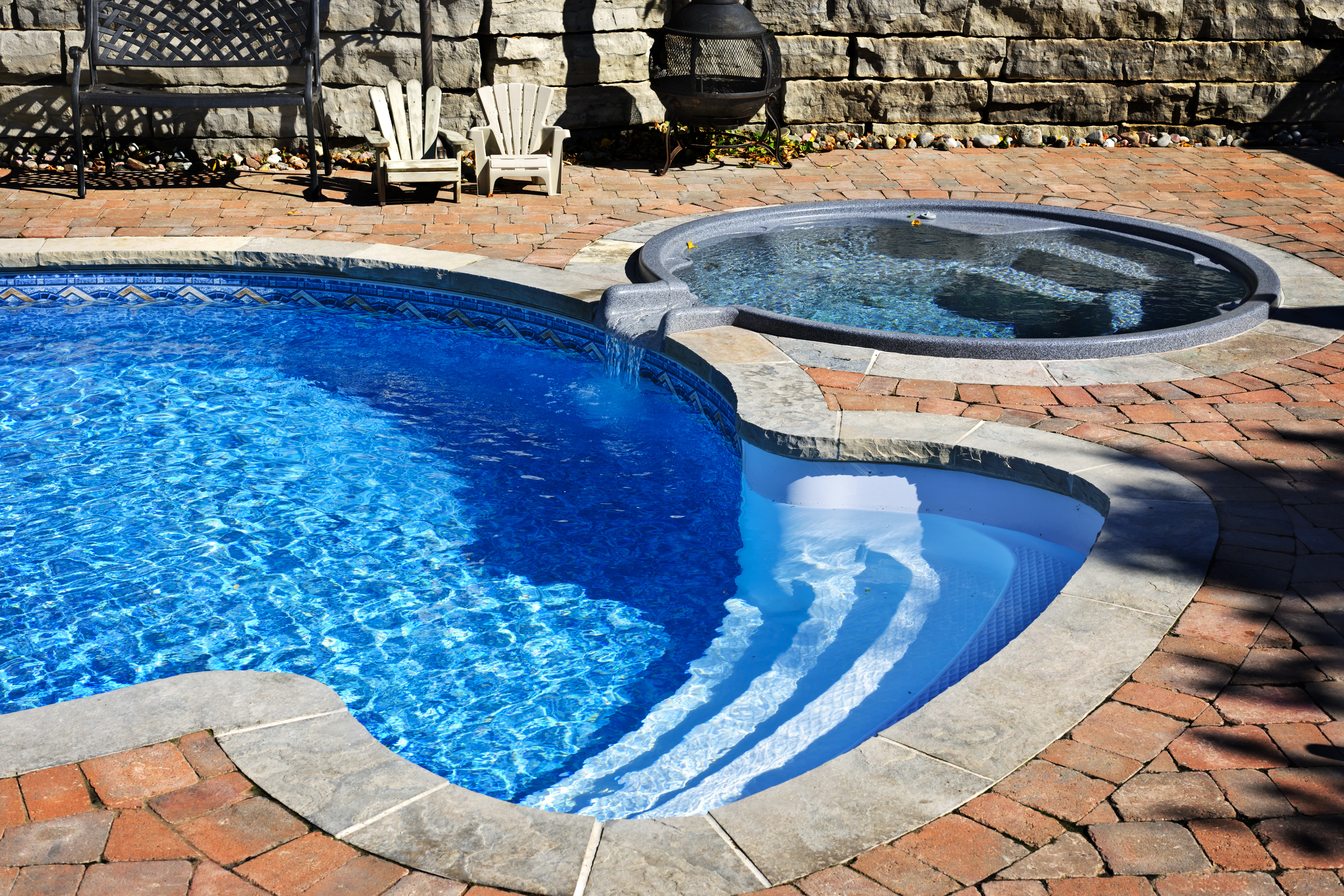 Outdoor inground residential swimming pool in backyard with hot tub